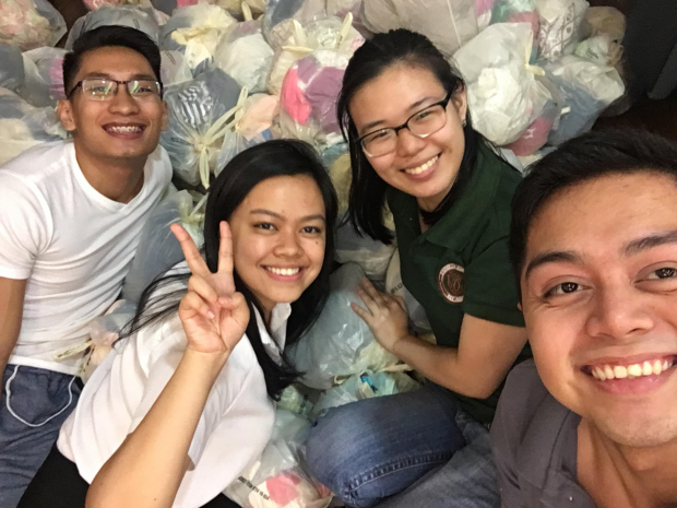 Student volunteers take a group picture after a well-spent night of repacking donations